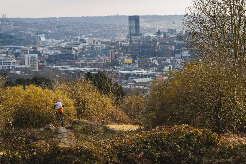 Rider on Parkwood Springs trail with views of Sheffield in the background